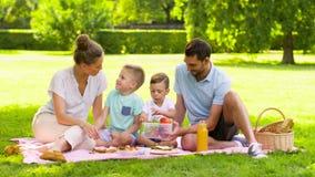 Gelukkige familie die vruchten op picknick eten bij park stock video
