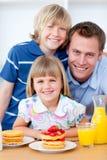Gelukkige familie die wafels met aardbeien eet Royalty-vrije Stock Afbeeldingen