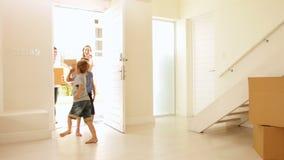 Gelukkige familie die zich in hun nieuw huis bewegen stock videobeelden
