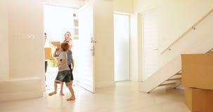 Gelukkige familie die zich in hun nieuw huis bewegen stock footage