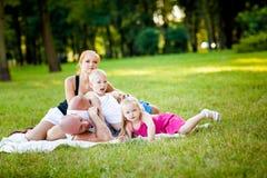 Gelukkige familie in een park stock foto's
