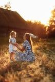 Gelukkige Familie Emotionele en vrolijke jonge moeder met haar weinig lachende dochter die op de regenboogzitting letten royalty-vrije stock afbeelding