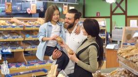 Gelukkige familie en hun leuke kleine dochter die baksel in de supermarkt kiezen stock video
