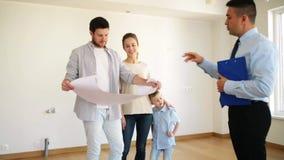 Gelukkige familie en makelaar in onroerend goed bij nieuw huis of flat stock footage