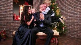 Gelukkige familie, familie met leuke baby op handen, oudste kindspelen met papa, Ouders met kinderen op de vooravond van nieuw stock video
