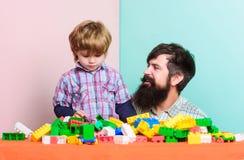 Gelukkige Familie Familievrije tijd Kindontwikkeling de bouwhuis met kleurrijke aannemer vader en zoonsspelspel royalty-vrije stock foto's