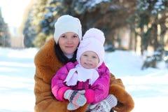 Gelukkige familie in gang: smilimg moeder en weinig dochter in de winter in openlucht Stock Afbeeldingen