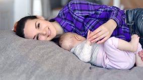 Gelukkige familie glimlachende moeder en weinig baby die op bed liggen die samen thuis ontspannen stock videobeelden
