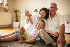 Gelukkige Familie Grootouders met kleindochter thuis Stock Foto's