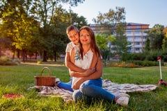Gelukkige familie het besteden tijd die in openlucht picknick in park hebben Moeder met haar en zoon die koesteren glimlachen Fam stock foto