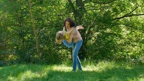 Gelukkige Familie het Besteden Tijd samen in het Park tijdens Sunny Warm Day Donkerbruine Moeder die en haar opnemen wervelen stock footage