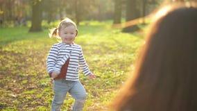 Gelukkige Familie het Besteden Vrije tijd samen in het Park Weinig Leuk Meisje met Twee Paardestaarten loopt aan Jonge Moeder en stock video