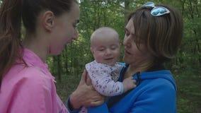 Gelukkige familie in het bos - de moeder kust haar baby en gelukkige grootmoeder stock videobeelden