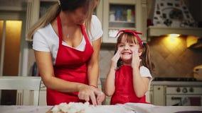 Gelukkige familie in het de keukenmamma en dochter in keuken het spelen met bloem om pret te hebben en de pasteitjes in te vormen stock footage