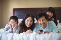 Gelukkige familie het letten op televisie in de bedruimte royalty-vrije stock afbeelding