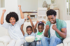 Gelukkige familie het letten op televisie die popcorn eten stock afbeeldingen