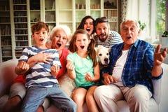 Gelukkige familie het letten op televisie in woonkamer stock fotografie