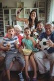 Gelukkige familie het letten op voetbalgelijke van meerdere generaties op televisie in woonkamer Royalty-vrije Stock Afbeelding