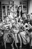 Gelukkige familie het letten op voetbalgelijke van meerdere generaties op televisie in woonkamer royalty-vrije stock fotografie