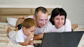 Gelukkige familie: het mamma, de papa en hun kleine zoon letten op een film op laptop, liggen op het bed en tonen emoties stock videobeelden