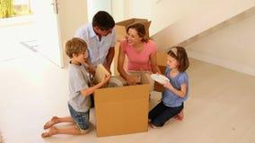 Gelukkige familie het openen doos in hun nieuw huis stock footage