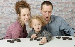 Gelukkige familie het spelen domino's Royalty-vrije Stock Afbeeldingen