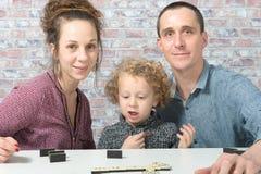 Gelukkige familie het spelen domino's Stock Foto's
