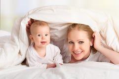 Gelukkige familie. Het spelen van de moeder en van de baby onder deken Stock Foto's