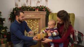 Gelukkige familie het vieren Kerstmis samen Moeder, vader en weinig babyzitting in de ruimte met Kerstmis stock footage