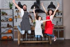 Gelukkige Familie in Keuken Het genieten van van ochtend Vader en dochter Meisje met ouders in schort Moeder en vader stock foto's