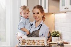 Gelukkige Familie in Keuken Moeder en kindbakselkoekjes Royalty-vrije Stock Afbeeldingen