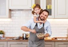 Gelukkige Familie in Keuken Vader en kind de dochter kneedt deeg a stock afbeeldingen