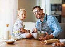 Gelukkige Familie in Keuken vader en kindbakselkoekjes stock foto