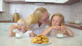 Gelukkige Familie Meisjes met blondehaar die melk en koekjes met hun moeder thuis in de keuken hebben Childs stock footage