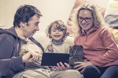 Gelukkige familie met babymeisje die een digitale tablet gebruiken Royalty-vrije Stock Foto's