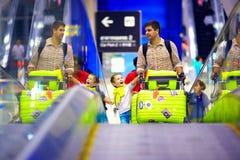 Gelukkige familie met bagage op transportband in luchthaven, klaar te reizen royalty-vrije stock fotografie