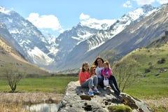 Gelukkige familie met een hond die in de bergen rusten stock afbeelding