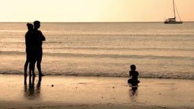 Gelukkige familie met een kind op vakantie bij het strand Over zonsondergang Slowmotion 1920x1080 stock footage