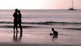Gelukkige familie met een kind op vakantie bij het strand Over zonsondergang Slowmotion 1920x1080 stock video