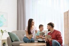 Gelukkige familie met geld bij lijst royalty-vrije stock afbeeldingen