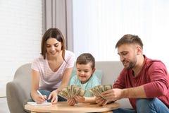 Gelukkige familie met geld bij lijst stock foto