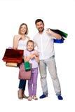 Gelukkige familie met het winkelen zakken die zich bij studio bevinden stock fotografie