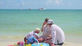 Gelukkige familie met kinderen die op het zandige strand met speelgoed spelen Tropisch eiland, op een hete dag stock videobeelden