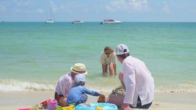 Gelukkige familie met kinderen die op het zandige strand met speelgoed spelen Tropisch eiland, op een hete dag stock video