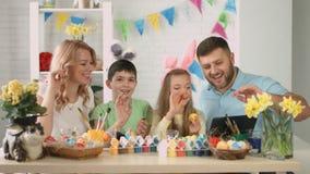 Gelukkige familie met kinderen die op Skype met verwanten voor Pasen spreken stock footage