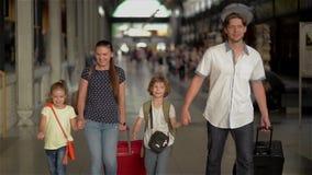 Gelukkige familie met kinderen die op station, ouders en jonge geitjes gaan die en op de luchthaven reizen lopen stock videobeelden