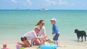 Gelukkige familie met kinderen en hond het spelen op het zandige strand met speelgoed Tropisch eiland, op een hete dag Royalty-vrije Stock Fotografie