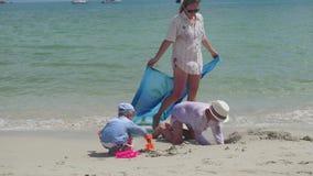 Gelukkige familie met kinderen en hond het spelen op het zandige strand met speelgoed Tropisch eiland, op een hete dag stock video