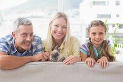Gelukkige familie met konijn op bank thuis Royalty-vrije Stock Afbeeldingen
