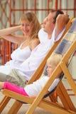 Gelukkige familie met meisje het doen leunen op chaise zitkamers Stock Fotografie